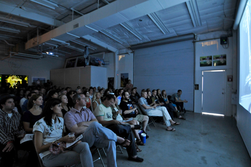 An audience in a warehouse-like space watching a film screening.