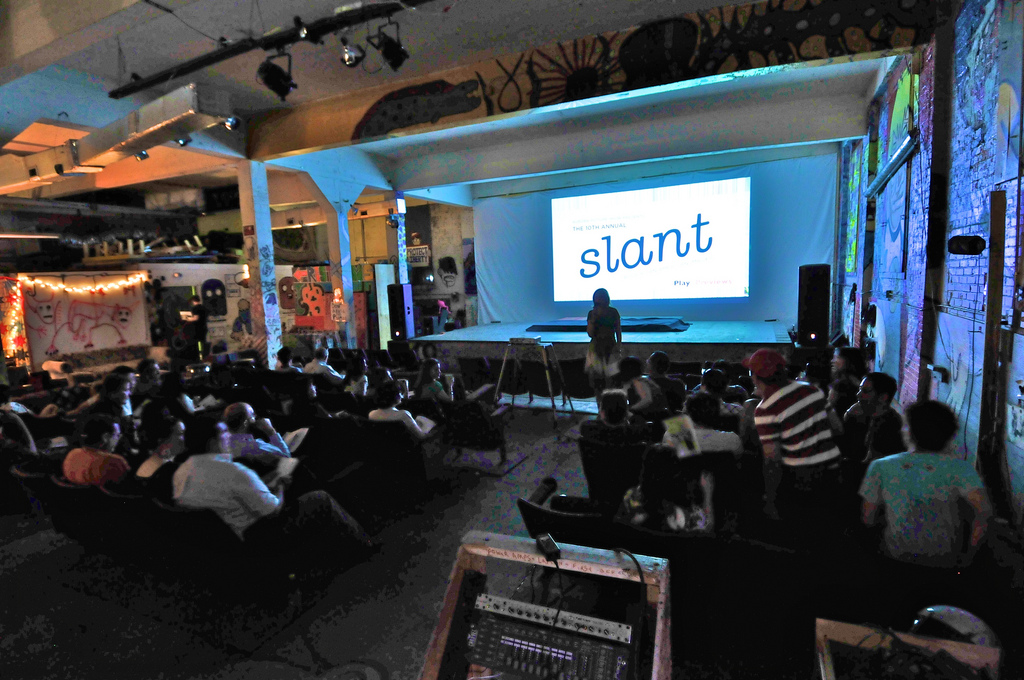 "An audience inside an art space watching a film screening. The words ""slant"" are on the screen."