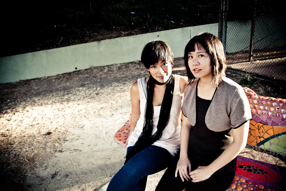 Two Asian American women sit next to each other at a public park.