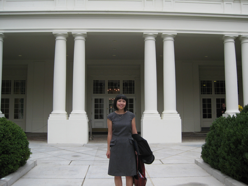 An Asian woman in a gray dress outside of an entrance to the White House.