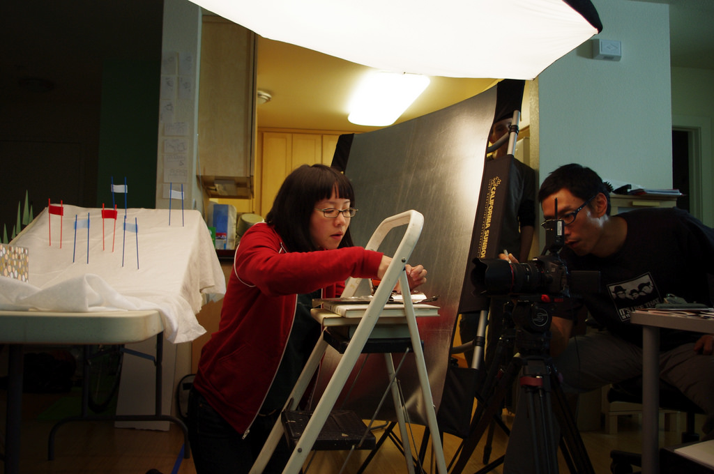 The set for a stop motion animation film. An Asian woman, the director, sets up the shot while an Asian man, the director of photography, adjusts the camera.