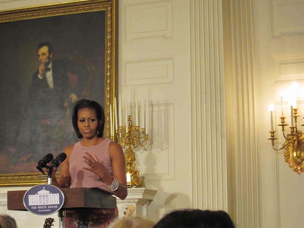 Michelle Obama in a sleeveless dress stands at a podium speaking in the White House. Behind her is a portrait of Abraham Lincoln.