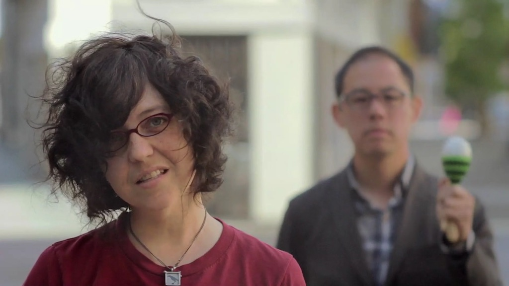 A still from a music video for The Invisible Cities. A white woman in a red shirt stands in the foreground. An Asian man stands in the background.