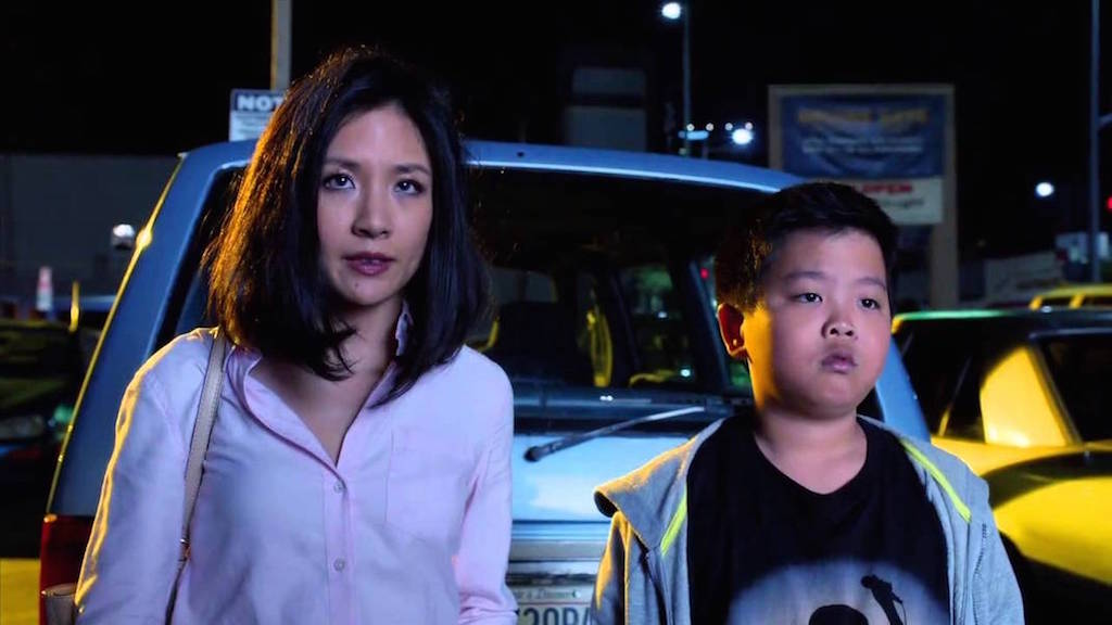 "Constance Wu and Hudson Yang as Jessica and Eddie in a scene from ""Fresh Off the Boat."" They are in a parking lot in the evening about to walk into a grocery store."