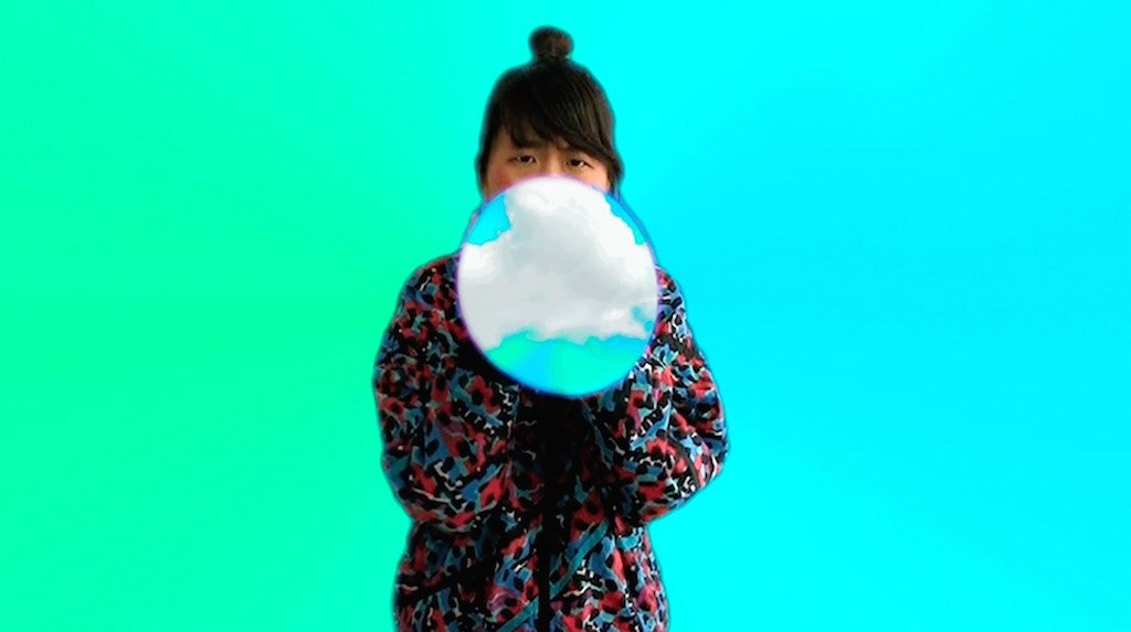 "A woman blows up a large bubble against a green and blue background in a still from the short film ""Moving to the Cloud"" by Laura Hyunjhee Kim."