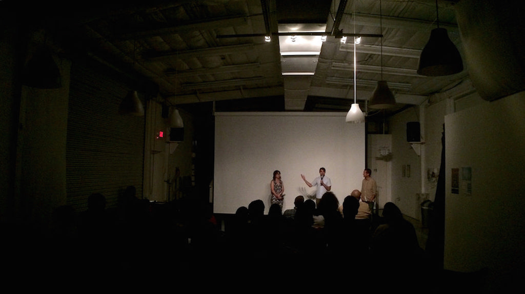 Three people stand in front of a large screen during the Q&A portion of a film screening.