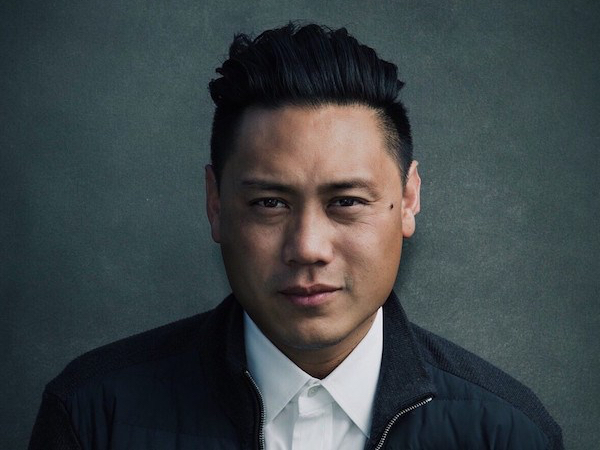 Photo of director Jon M. Chu. He is an East Asian man, looking at the camera, wearing a white shirt and black jacket.