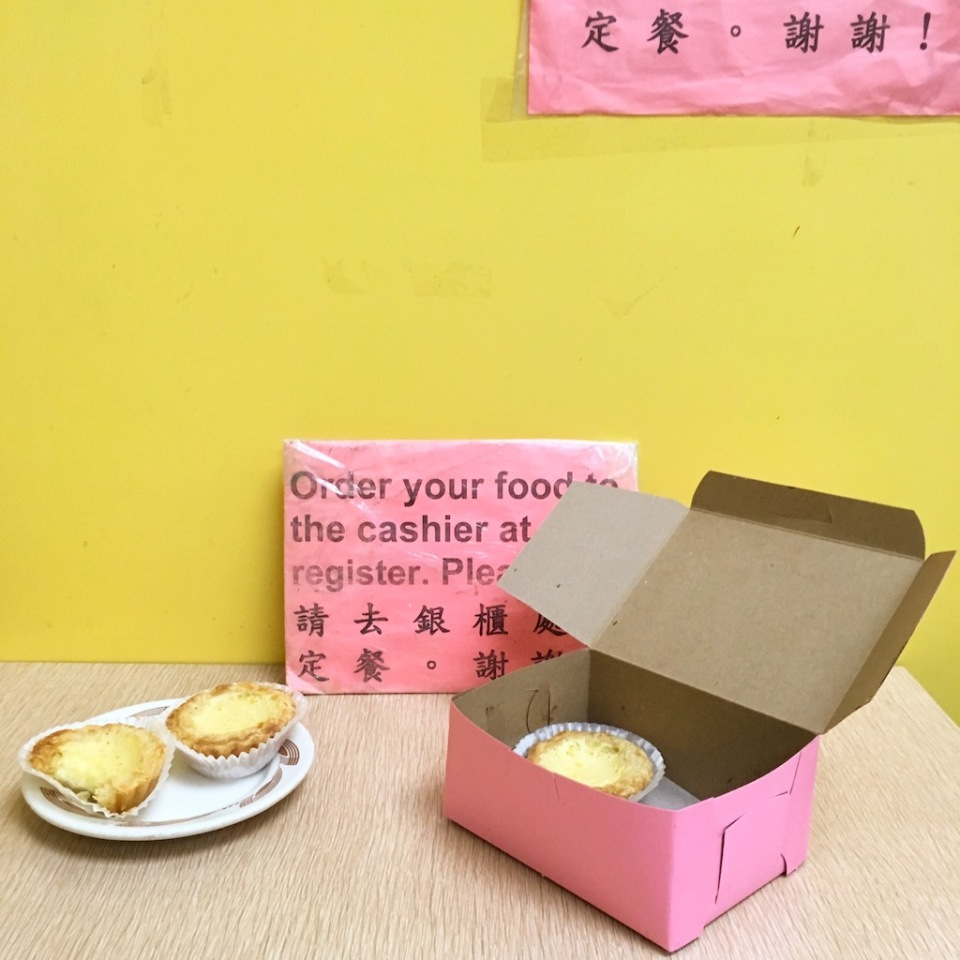 An open pink bakery box with one dan tat inside, and two more on a plate. The wall behind it is yellow.