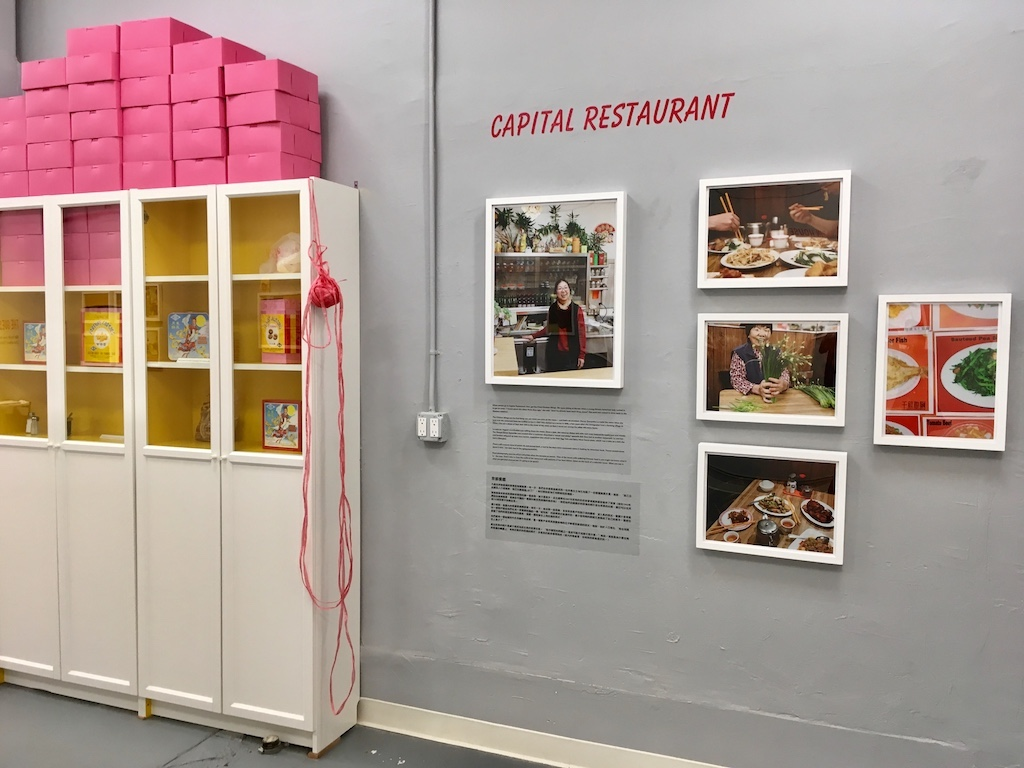 A photo exhibit inside a gallery. A few photos of Capital Restaurant are on the wall. There is also a cabinet with pink bakery boxes stacked on it.
