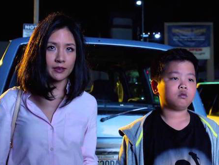 A still from Fresh Off the Boat featuring Constance Wu and Hudson Yang. They are in a parking lot looking out towards something.