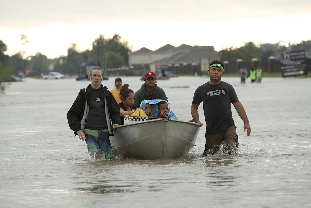 Three men of various racial backgrounds push a boat with a woman and two children sitting in it through knee-high water in the streets of Houston.