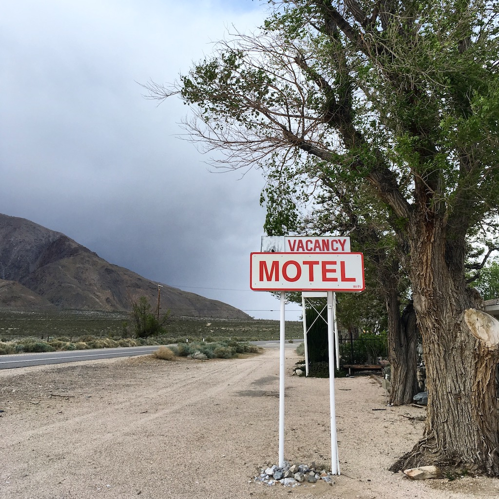 "A sign by the side of an empty road reads, ""Vacancy, Motel."""
