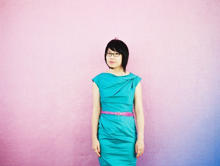 Photo portrait of Melissa Hung, an Asian American woman, standing against a pink wall.