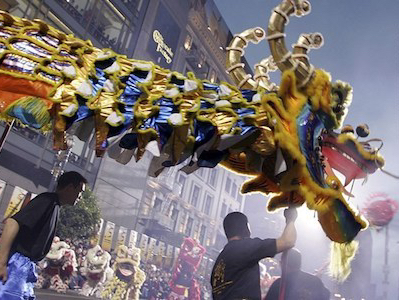 Photo of a large dragon puppet being carried by multiple people at a Chinese New Year parade.