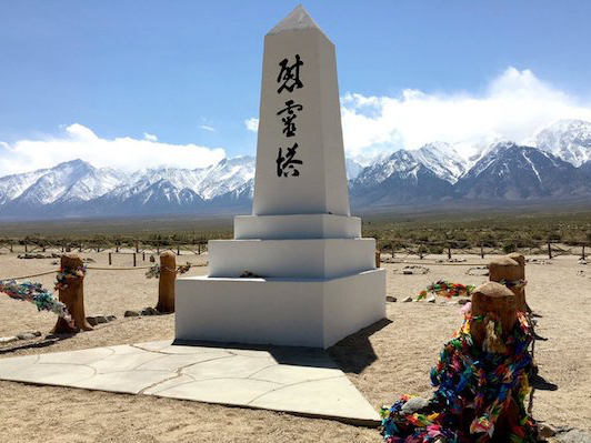 Photo of a monument with Japanese characters on it at Manzanar. There are snow-capped mountains in the background.
