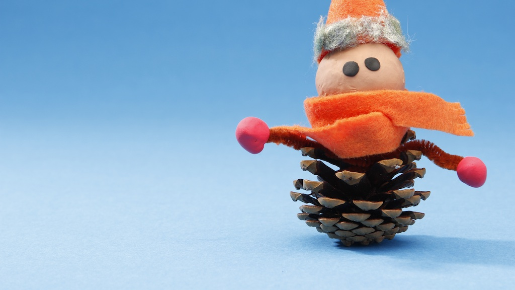 "A still from an animation for ""Stitched,"" showing a pinecone with a clay head with black eyes on top of it, wearing an orange scarf and hat."