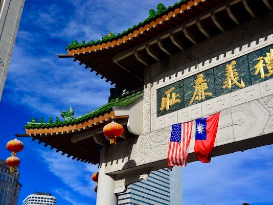 Photo of a Chinese-style gate with eaves curling up. There are lanterns, as well as an American and Taiwanese flag hanging from it.