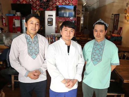 Photo of 3 Uighur men standing in their restaurant. There are tables behind them.