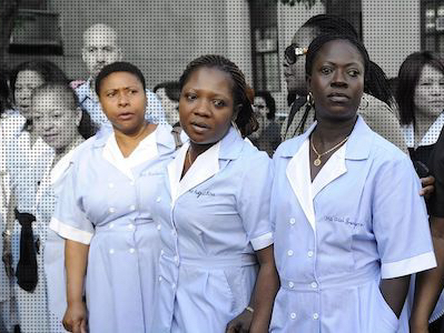 Photo illustration of several people standing outside. Three of them in the front of black and in color (the other people are in black and white.) The three in color are wearing blue maid uniforms.
