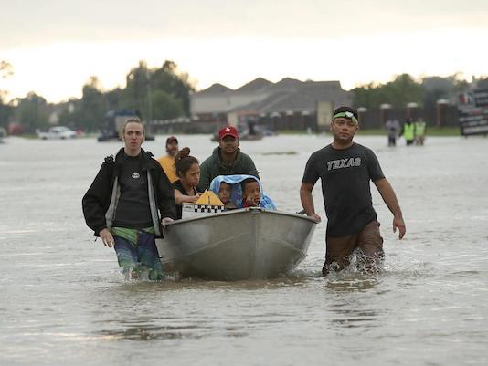 Photo of three people pushing a boat in knee-high water. Inside the boat are a woman and two children with a blanket around them.