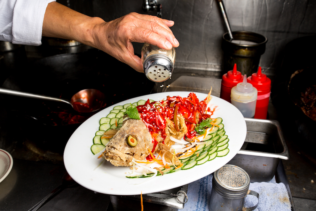 A cooked fish on a platter with cucumber slices artfully arranged around it. A hand holds a jar of seasoning over the platter. Photo by Michelle Min.