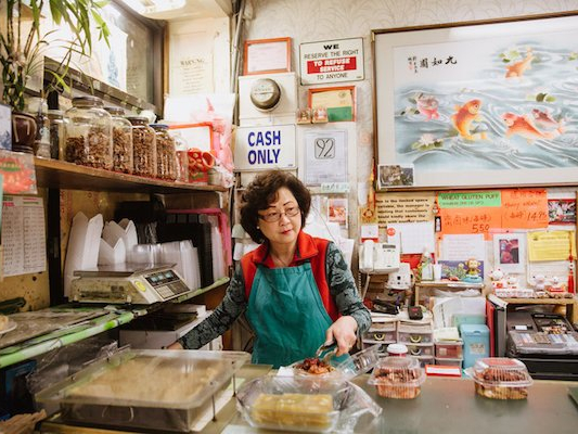 Gentrification of Chinatowns. Photo by Andria Lo. A middle-aged Asian woman wearing glasses and an apron stands behind the counter of a store selling food. She has tongs in one of her hands.