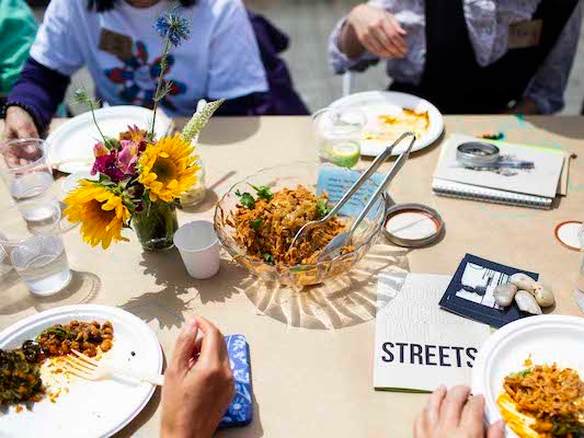 The People's Kitchen Collective. Photo by Sana Kaveri Kadri. A clear bowl of shredded meat on a table. There are tongs in the bowl, and a glass jar with flowers next to the bowl. There are diners around the bowl but only their hands are visible.