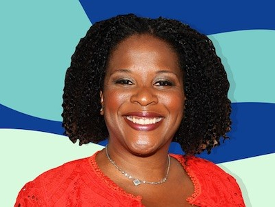 Interview with Tayari Jones for Shondaland. Tayari Jones, a black woman, smiling. The photo shows her from the shoulders up, against an illustrated background of blue colors. She is wearing a red dress and a necklace.