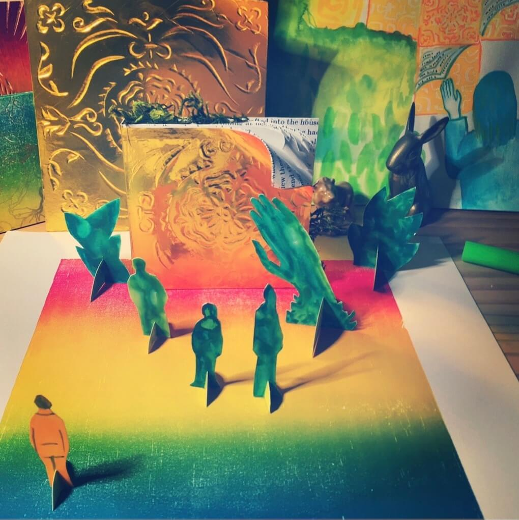 Image of a dimensional artwork with a multicolor base, and figures of people standing on it. There is also a bunny sculpture and some gold-colored wall-like objects.