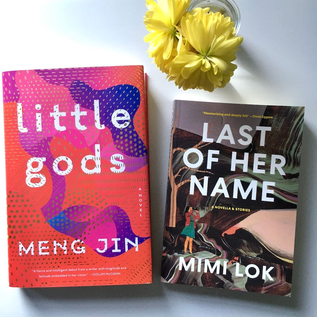 KSW Presents: Meng Jin and Mimi Lok. The books Little Gods by Meng Jin and Last of Her Name by Mimi Lok on a white surface. There are small yellow flowers in a clear bud vase.