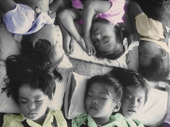 Photo of six children napping on a floor, each on their own pillow.