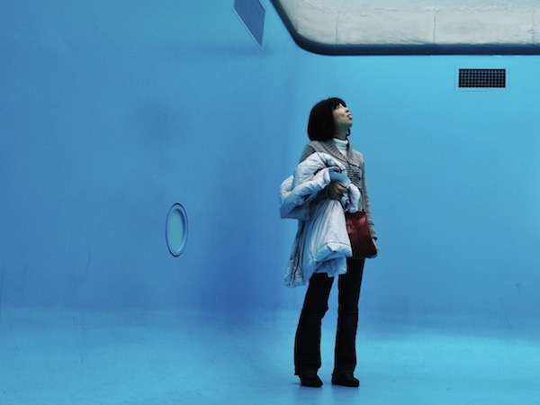 A woman with dark hair holding a coat over an arm. She is in the bottom of a art installation that looks like the bottom of a pool.