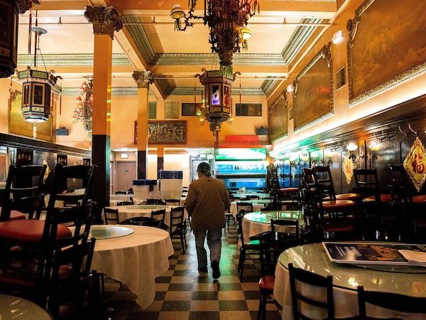 A man with his back to the camera walks through an empty restaurant, the Far East Cafe